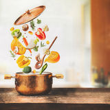 Healthy vegetarian eating and cooking with various flying chopped vegetables ingredients, cooking pot and spoon at table desk at Stock Image