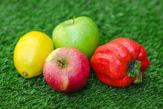 Healthy vegetarian food: the composition of fruits and vegetables in the background of green grass Stock Photo