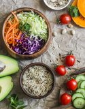 Healthy vegetarian food set background. Cabbage salad, avocado, tomatoes, cucumbers, pumpkin, wild rice on a paper background, top. View. Flat lay royalty free stock images