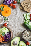 Healthy vegetarian food set background with free space for text. Cabbage, avocado, tomatoes, cucumbers, pumpkin, wild rice on a pa. Per background, top view Stock Photo