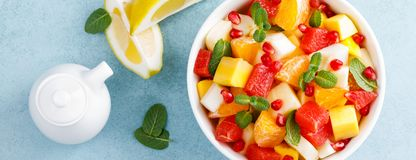 Healthy vegetarian fresh fruit salad with apple, pear, tangerine, grapefruit, mango, pomegranate and lemon juice. Top view. Banner. Healthy vegetarian fresh stock photo
