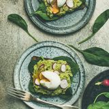 Healthy vegetarian gluten-free breakfast toasts flat-lay, square crop. Healthy vegetarian breakfast flat-lay. Whole-grain toasts with avocado, spinach and Royalty Free Stock Photography