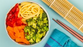 Healthy Vegetarian Hawaiian Style Food Bowl. Healthy Vegetarian Hawaiian Style Buddha Food Bowl With Broccoi Carrots Red Peppers and Egg Noodles Against A Blue stock image