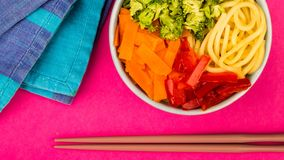 Healthy Vegetarian Hawaiian Style Food Bowl. Healthy Vegetarian Hawaiian Style Buddha Food Bowl With Broccoi Carrots Red Peppers and Egg Noodles Against A Pink royalty free stock photo