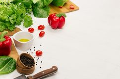 Healthy vegetarian ingredients for spring fresh green salad and kitchenware on white wood table, copy space. Spring vitamin dieting food Royalty Free Stock Photos