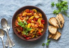 Healthy vegetarian lunch - stewed garden vegetables. Vegetable ratatouille and grilled bread. On a blue background. Top view stock photo
