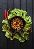 Healthy vegetarian meal. Chanterelle mushrooms fried in cast iron pan with onion served with lettuce and chili pepper on dark. Background copyspace above view stock photography