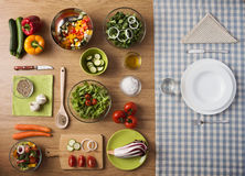Healthy vegetarian meal. Concept with table set, fresh raw vegetables and dishware Royalty Free Stock Image