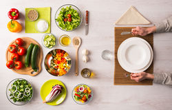 Healthy vegetarian meal. Concept with table set, hands holding fork and knife and fresh raw vegetables Royalty Free Stock Photography