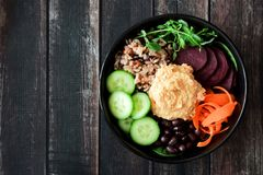Healthy vegetarian nourishment bowl on dark wood. Healthy vegetarian nourishment bowl with hummus, beans, wild rice, beets, carrots, cucumbers and pea shoots Royalty Free Stock Photos