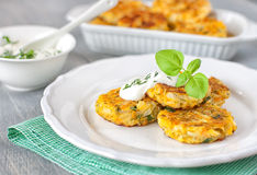 Healthy vegetarian patties. Healthy vegetarian cabbage patties with carrot, onion and green against the backdrop of sour cream sauce with herbs Stock Photo
