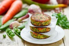 Healthy vegetarian patties made from potatoes, carrots, onions, green peas, herbs and spices. Selective focus stock photo