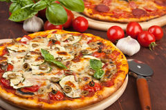 Healthy vegetarian pizza. Healthy vegetables and mushrooms vegetarian pizza with Olives and Fresh Basil and salami pizza at the back Stock Image