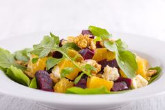 Healthy vegetarian salad with beetroot, green arugula, orange, feta cheese and walnuts on plate Stock Photos