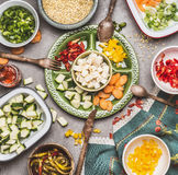 Healthy vegetarian salad preparation with Diced feta cheese, cut vegetables and pearl barley , top view Stock Photo