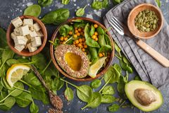 Healthy vegetarian salad with tofu, chickpea, avocado and sunflower seeds. Healthy vegan food concept. Dark background, top