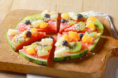 Healthy vegetarian tropical fruit watermelon pizza. Low angle view of a healthy vegetarian and vegan tropical fruit watermelon pizza topped with kiwifruit Stock Images