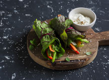 Healthy vegetarian vegetables rolls and yoghurt sauce on a wooden cutting board Royalty Free Stock Photos
