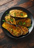 Healthy vegeterain Oven baked aubergines, Eggplant with parsley and herbs in a black plate.  stock images