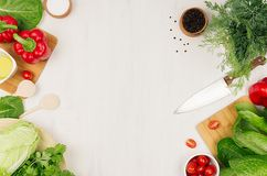 Healthy vegeterian ingredients for spring fresh green salad and kitchenware on white wood board, top view, copy space. Spring vitamin dieting food stock photography