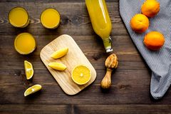 Healthy vitamin drink. Fresh orange juice near fruits and juicer on dark wooden background top view.  Royalty Free Stock Images