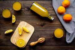 Healthy vitamin drink. Fresh orange juice near fruits and juicer on dark wooden background top view.  Stock Photo