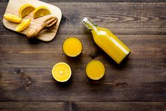 Healthy vitamin drink. Fresh orange juice near fruits and juicer on dark wooden background top view.  Royalty Free Stock Image