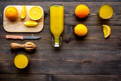 Healthy vitamin drink. Fresh orange juice near fruits and juicer on dark wooden background top view copyspace. Healthy vitamin drink. Fresh orange juice near Royalty Free Stock Images