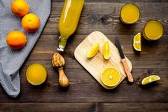 Healthy vitamin drink. Fresh orange juice near fruits and juicer on dark wooden background top view.  Stock Photography