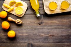 Healthy vitamin drink. Fresh orange juice near fruits and juicer on dark wooden background top view copyspace. Healthy vitamin drink. Fresh orange juice near Stock Image
