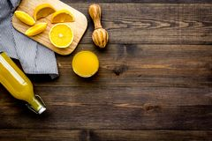 Healthy vitamin drink. Fresh orange juice near fruits and juicer on dark wooden background top view copyspace. Healthy vitamin drink. Fresh orange juice near Stock Photo