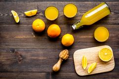 Healthy vitamin drink. Fresh orange juice near fruits and juicer on dark wooden background top view copyspace. Healthy vitamin drink. Fresh orange juice near Royalty Free Stock Photo