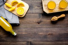 Healthy vitamin drink. Fresh orange juice near fruits and juicer on dark wooden background top view copyspace. Healthy vitamin drink. Fresh orange juice near Stock Images