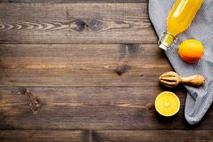Healthy vitamin drink. Fresh orange juice near fruits and juicer on dark wooden background top view copy space. Healthy vitamin drink. Fresh orange juice near Royalty Free Stock Photography