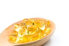 Daily health vitamins. Healthy vitamins are golden yellow on a white background Royalty Free Stock Image