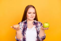 Healthy vs unhealthy eating. Portrait of thoughtful pensive mind royalty free stock images