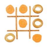 Healthy vs unhealthy food. Tic-tac-toe game. Carrots versus bagels Stock Photo