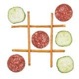 Healthy vs unhealthy food. Tic-tac-toe game, cucumber versus salami, salami wins Stock Photos