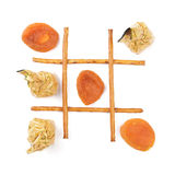 Healthy vs unhealthy food. Tic-tac-toe game. Sweets versus dried apricots Royalty Free Stock Photography