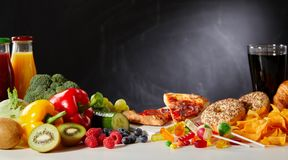 Healthy vs unhealthy foods with copy space. Fruit, vegetables, pastries and sweets in a healthy vs unhealthy foods concept with a dark background and copy space stock photos