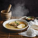 Healthy and warming winter soup with rice, carrot, chickpeas, chicken, ham and boiled egg over rustic background. Spanish soup Puchero Andaluz. Winter food Stock Photos