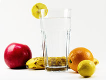 Healthy water and fruit vitamines. Glas of pure water with orange, lemon, banana and apple Royalty Free Stock Photography