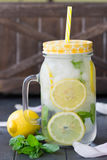 Healthy water with mint, sliced lemons and cucumbers. Diet drink. Sassy water. Mason jar full with sliced fruits and vegetables. Royalty Free Stock Images