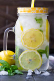 Healthy water with mint, sliced lemons and cucumbers. Diet drink. Sassy water. Mason jar full with sliced fruits and vegetables. Stock Photo