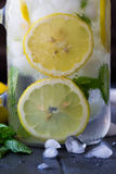 Healthy water with mint, sliced lemons and cucumbers. Diet drink. Sassy water. Mason jar full with sliced fruits and vegetables. Stock Images