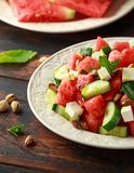 Healthy Watermelon, Cucumber Salad with Mint, pistachios nuts and feta cheese. rustic wooden background royalty free stock image