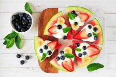 Summer watermelon pizza with blueberries, strawberries, bananas and yogurt, top view table scene against white wood. Healthy watermelon pizza with blueberries royalty free stock photo