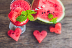 Healthy watermelon smoothie with mint, a piece of watermelon, hearts and a striped straw on a wood background.  Royalty Free Stock Photography