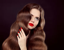 Healthy wavy hair. Beautiful model girl, beauty portrait with sh. Iny brown straight long hairstyle and red lips makeup isolated on black background. Elegant Royalty Free Stock Photography