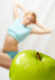 Healthy way of life. The green apple in the foreground, on a background the young girl goes in for sports royalty free stock photography